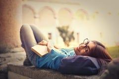 Mujer joven con el pelo largo que se sienta en la lectura del asiento de ventana Imagen de archivo libre de regalías