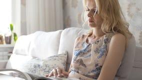 Mujer joven con el pelo largo que se sienta en la lectura del asiento de ventana imagen de archivo