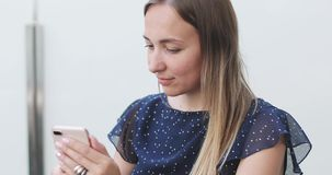 Mujer joven con el pelo largo que se sienta en un balcón abierto y que escribe un mensaje en un teléfono móvil metrajes