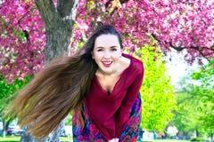 Mujer joven con el pelo largo que sonríe en cámara delante de Sakura Foto de archivo libre de regalías
