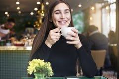 Mujer joven con el pelo largo que sonríe, taza de consumición del café en las manos que tienen resto en café cerca de ventana Imagenes de archivo