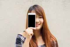Mujer joven con el pelo marrón que sonríe mostrando una pantalla en blanco del smartphone que se coloca en fondo del muro de ceme fotografía de archivo libre de regalías