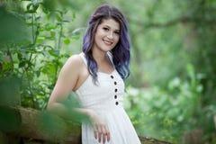 Mujer joven con el pelo moreno y púrpura en un parque verde Imagen de archivo