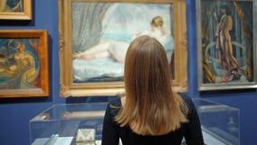 Mujer joven con el pelo recto que mira una imagen con Venus en el museo almacen de video