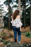 Mujer joven con el pelo rizado que camina a través del bosque imagenes de archivo