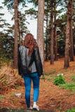 Mujer joven con el pelo rizado y la chaqueta negra que camina a través del bosque foto de archivo libre de regalías