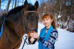 Mujer joven con el pelo rojo en un caballo en invierno foto de archivo