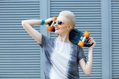 Mujer joven con el pelo rubio corto que sonríe en el fondo de la moda y que sostiene poco monopatín del penique detrás de su cabe Foto de archivo libre de regalías