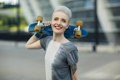 Mujer joven con el pelo rubio corto que sonríe en el fondo de la moda y que sostiene poco monopatín del penique detrás de su cabe Imágenes de archivo libres de regalías