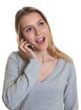 Mujer joven con el pelo rubio que habla en el teléfono Foto de archivo libre de regalías
