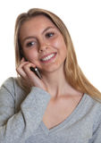 Mujer joven con el pelo rubio que sonríe en el teléfono Fotografía de archivo libre de regalías