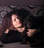 Mujer joven con el perro de caniche de juguete en un sofá en un cuarto oscuro imagenes de archivo
