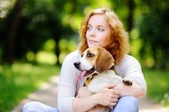 Mujer joven con el perro del beagle en el parque del verano Foto de archivo