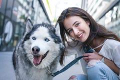 Mujer joven con el perro en ciudad Fotografía de archivo libre de regalías