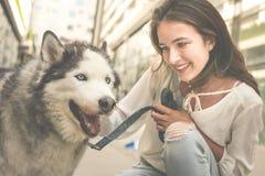 Mujer joven con el perro en ciudad Actitudes de la muchacha del adolescente con su perro Foto de archivo libre de regalías