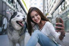 Mujer joven con el perro en ciudad Muchacha del adolescente que toma la imagen del uno mismo Imagen de archivo