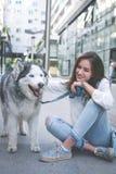Mujer joven con el perro en ciudad Muchacha del adolescente con su perro Foto de archivo