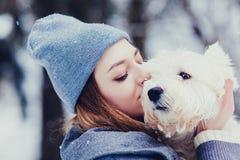 Mujer joven con el perro en invierno imagenes de archivo