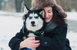 Mujer joven con el perro fornido en el parque del invierno Imagenes de archivo
