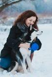 Mujer joven con el perro fornido en el parque del invierno Imagen de archivo
