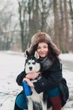 Mujer joven con el perro fornido en el parque del invierno Foto de archivo