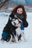 Mujer joven con el perro fornido en el parque del invierno Imágenes de archivo libres de regalías