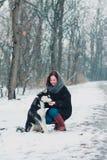 Mujer joven con el perro fornido en el parque del invierno Fotografía de archivo
