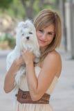 Mujer joven con el perro maltés del animal doméstico Fotos de archivo libres de regalías