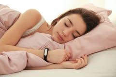 Mujer joven con el perseguidor del sueño que descansa en cama fotos de archivo