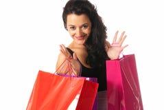 Mujer joven con el primer de los bolsos de compras aislado en el fondo blanco Foto de archivo