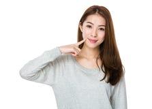 Mujer joven con el punto del finger a sus dientes Imágenes de archivo libres de regalías