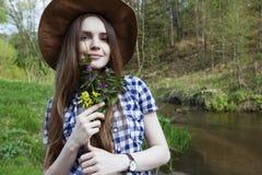 Mujer joven con el ramo de flores salvajes Imagen de archivo
