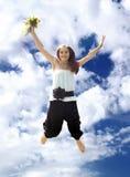 Mujer joven con el ramo en salto Fotos de archivo libres de regalías
