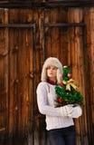 Mujer joven con el árbol de navidad en el frente de la pared de madera rústica Imagen de archivo libre de regalías
