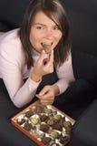 Mujer joven con el rectángulo de chocolates imagen de archivo