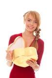 Mujer joven con el rectángulo de regalo abierto del oro como corazón Fotos de archivo