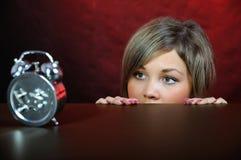 Mujer joven con el reloj. Foto de archivo libre de regalías
