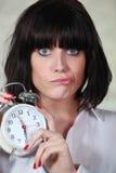 Mujer joven con el reloj de alarma fotografía de archivo