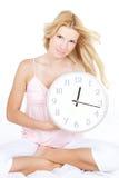 Mujer joven con el reloj en la cama Imagen de archivo libre de regalías
