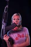 Mujer joven con el rifle automático Imagenes de archivo