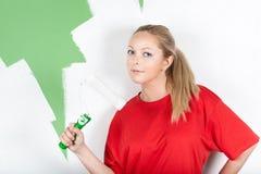 Mujer joven con el rodillo de pintura a disposición Foto de archivo
