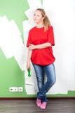 Mujer joven con el rodillo de pintura a disposición Imagen de archivo libre de regalías