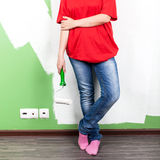 Mujer joven con el rodillo de pintura a disposición Fotografía de archivo libre de regalías