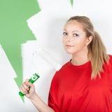 Mujer joven con el rodillo de pintura a disposición Imágenes de archivo libres de regalías