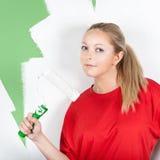 Mujer joven con el rodillo de pintura a disposición Imagen de archivo