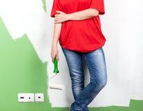 Mujer joven con el rodillo de pintura a disposición Foto de archivo libre de regalías