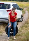 Mujer joven con el sittign quebrado del coche en la rueda de repuesto y la llamada del servicio auto para la ayuda Fotografía de archivo