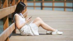 Mujer joven con el smartphone al aire libre en el parque que se sienta en el puente metrajes