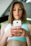 Mujer joven con el smartphone en el gimnasio, rotura del entrenamiento Imagenes de archivo