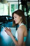 Mujer joven con el smartphone en el gimnasio, rotura del entrenamiento Fotos de archivo libres de regalías